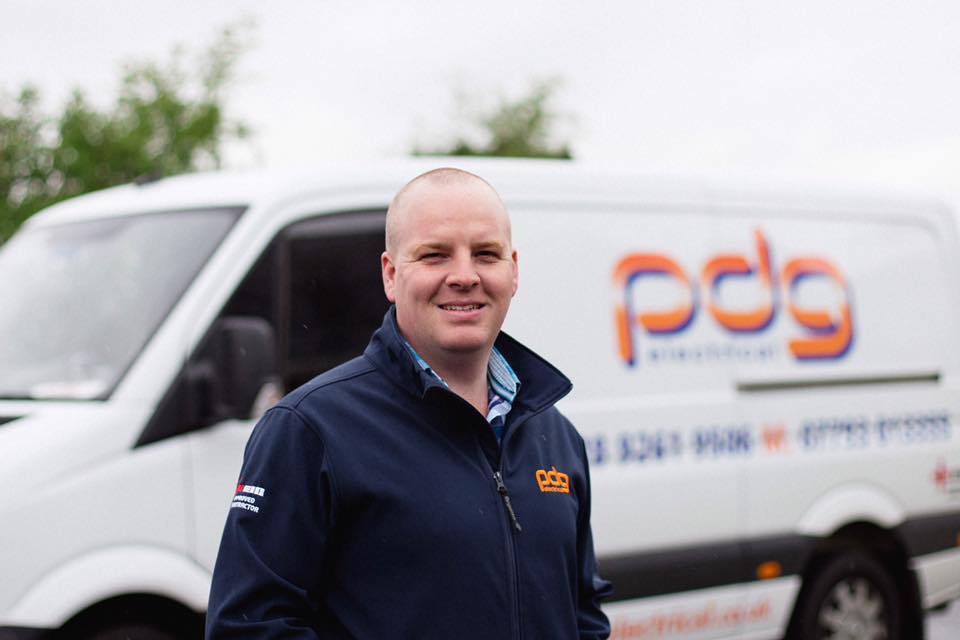 Photo of Phil standing in front of PDG Electrical van